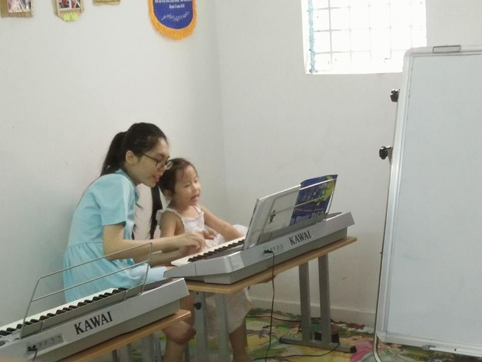 Cô Ngọc Lê đang hướng dẫn bé những nốt nhạc trên bàn phím.